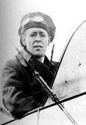 Half-portrait of man in cap and goggles seated in the open cockpit of a biplane