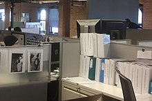 Thick white binders in a cubicle, three people are visible, exposed brick walls