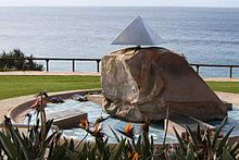 A large stone sitting in a circular basin. The stone is capped with a small metal pyramid. Four plaques also sit in the basin. The entire memorial is located on a hill, with flowers in the foreground and the ocean behind.