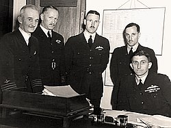 Five men in dark military uniforms behind a desk, four of whom are standing and one sitting