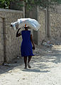 A Haitian woman carries supplies on her head that were distributed in Petit Place Cazeau, Port-au-Prince, Haiti 100223-N-HX866-006.jpg
