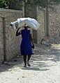 A Haitian woman carries supplies on her head that were distributed in Petit Place Cazeau, Port-au-Prince, Haiti 100223-N-HX866-006.jpg