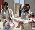 A man carrying a child with a bandaged leg leaves the Egyptian Field Hospital at Bagram Airfield, in Parwan province, Afghanistan, May 29, 2011 110529-A-IB797-057.jpg