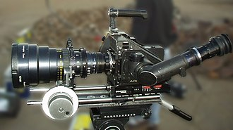 Follow focus - An Arri 35mm film camera with a follow focus mechanism mounted to a zoom lens.