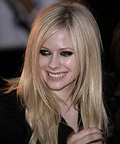 A picture of a blonde woman looking to her right wearing a black shirt and smiling