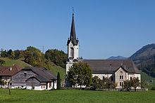 Une église avec un haut clocher sur un champ vert