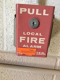 A Notifier pull station at Oklahoma State University. The orange sticker on it warns would-be pranksters the consequences for false alarms.