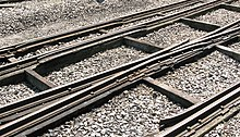 Three rails cross the picture from left to right supported on thick timbers; occasional smaller timbers cross between these and stone chippings fill the space between them.