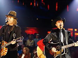 Two men playing guitars and singing into microphones, one in a brown felt hat and striped top and the other in a black cowboy hat and dark jacket