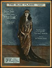 Sheet music cover showing a white woman with long, dark hair, dressed in a floor-length patterned gown and matching headpiece; her image is surrounded by text giving credits for the play and song.