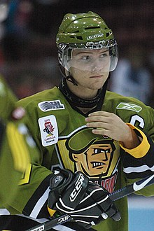 A frontal view of a white, teenage ice hockey player during a game. He is wearing a green, visored helmet and an olive green jersey with a logo consisting of an animated face of a soldier. He appears calm while looking to the right and is reaching for his face with his right hand.