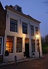Gepleisterde lijstgevel voor huis van parterre en verdieping, waarop schilddak met dakvenster met vleugelstukken. Gestoken deurkalf, muurijzers en stoep
