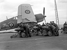 Black and white photograph of a group of men pushing bombs on trolleys on the deck of an aircraft carrier at sea. A single-engined aircraft is located immediately behind the men.