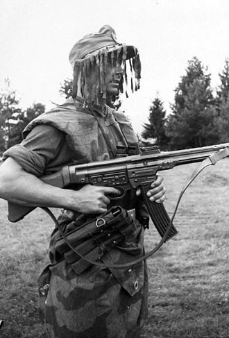 "StG 44 - A German infantryman armed with an StG 44, wearing ""splinter"" camouflage and a ghillie cap in 1944."