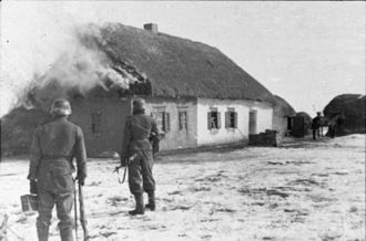 Third Battle of Kharkov - Waffen-SS men near a burning house, Kharkov, February 1943.