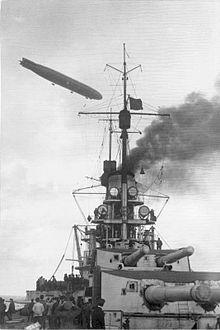 The gun turrets of a battleship. A gray zeppelin flies overhead