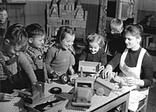 Four kindergarten children play with toy trucks on a table and a teacher sits with them while they play
