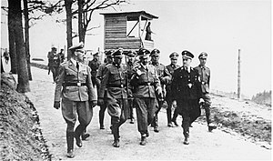 Austrian SS - With Kaltenbrunner (on the far left), Heinrich Himmler talks to camp commander, Franz Ziereis, during an official visit to Mauthausen concentration camp in 1941. Austrian Gauleiter August Eigruber (wearing a pre-war Allgemeine SS uniform) accompanies them along with other SS officials.