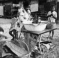 COLLECTIE TROPENMUSEUM Een vrouw verkoopt in bananenblad verpakte nasi ketan te Tulehu TMnr 20000285.jpg