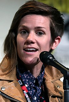 Cameron Esposito speaking into a microphone. She is Caucasian, has an asymmetrical haircut, and is wearing a leather jacket.
