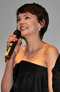 A woman stands and smiles, holding a microphone