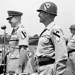 Two soldiers stand at attention. The one on the right wears an American uniform and helmet bearing the patch of the 1st Cavalry Division. The one on the left wears an Australian uniform with peaked cap and generals' gorget patches and carries a swagger stick, but incongruously also wears the patch of the 1st Cavalry Division on his sleeve.