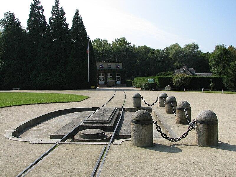Clairière de l'Armistice, appelée aussi clairière de Rethondes. Au premier plan, l'emplacement où se trouvait le wagon de l'Armistice, au second plan, le musée de l'Armistice qui abrite un wagon identique.
