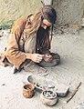 Costumed bronze-age re-enactor knapping stone tools.jpg