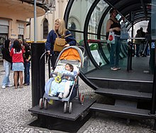 a woman with a baby carriage uses a platform lift to access a station above street level