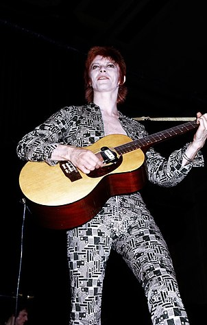 A color photograph of David Bowie with an acoustic guitar