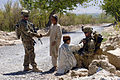 Defense.gov News Photo 110401-A-DE255-002 - U.S. Army Cpl. Anthony Gomez left shakes the hand of a young resident of Tarok Kolache while Pfc. Roy Heggernes right interacts with a young boy.jpg
