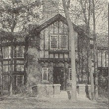 A two-story Tudor style building in a forest of tall trees