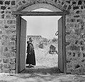 Een franciscaner monnik bij een geopende poort met het gezicht op de deels gerec, Bestanddeelnr 255-1548.jpg