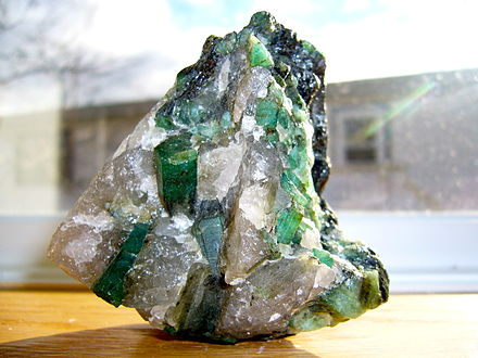 Brazilian emerald (grass-green variety of the mineral beryl) in a quartz-pegmatite matrix with typical hexagonal, prismatic crystals. Emerald in a quartz and pegmatite matrix.JPG