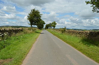 A parliamentary enclosure road near Lazonby in Cumbria. The roads were made as straight as possible, and the boundaries much wider than a cart width to reduce the ground damage of driving sheep and cattle. Enclosure Road, Lazonby.jpg