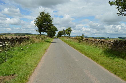 A parliamentary enclosure road near Lazonby in Cumbria. The roads were made as straight as possible, and the boundaries much wider than a cart width to reduce the ground damage of driving sheep and cattle.