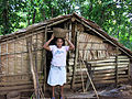 Esta Mamae carries pana in a basket on her head outside a traditional food storage hut. (10694583373).jpg