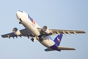 A FedEx Airbus A300 with condensation in both intakes, with its gear retracting.