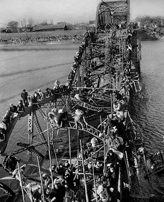 Flight of refugees across a wrecked bridge in Korea