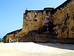 A fortified, but badly-faded yellow-coloured wall looks off into distant sea to the left.