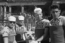 A black and white photograph of four cyclists wearing jerseys with Gitane–Leroux insignia.