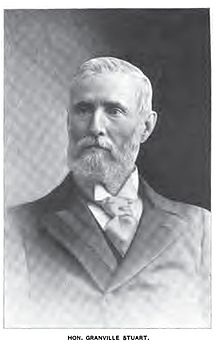 B&W photograph of a grey haired man with a full beard.