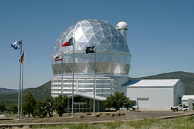 A silver geodesic dome against a blue sky, with flags in the foreground.