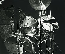 Stuart is seated behind and obscured by his kit. He is looking forward, a drumstick is visible in his left hand.