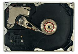 The inside of a hard disk drive with the platter (disk) removed.   To the left is the read-write arm. In the middle the electromagnets of the platter's motor can be seen.