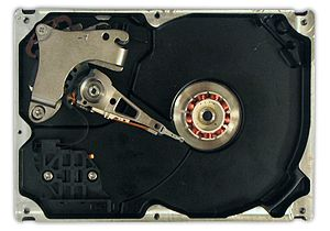 Hard disk drive - HDD with disks and motor hub removed exposing copper colored stator coils surrounding a bearing in the center of the spindle motor. Orange stripe along the side of the arm is thin printed-circuit cable, spindle bearing is in the center and the actuator is in the upper left