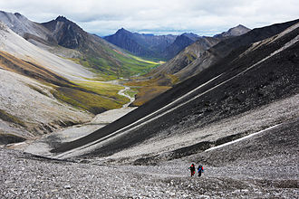 Gates of the Arctic Wilderness - A pair of hikers climbs toward a high pass in the Central Brooks Range.