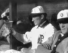 "A man in a white baseball jersey and white baseball cap with a dark brim and an Old English ""D"" on the front points at something off-camera with his right hand."