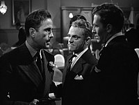 Close up shot of three men in a room talking.