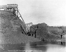 Добыча в ручье с помощью гидравлического подъемника, 1905 год, изображающий человека рядом с машиной высотой 50 футов, которая всасывала гравий со дна ручья и создавала пропасть.